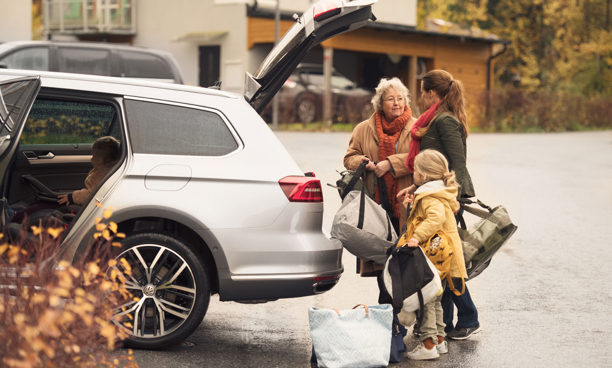 Grandmother, mother and child packing up the car.
